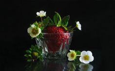 Натюрморт с ягодой клубники в стеклянной вазочке с цветами. На черном фоне. От Estella