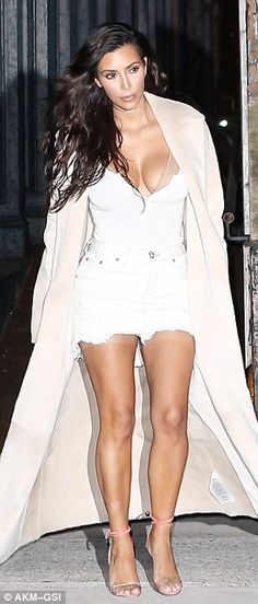 The reality star wore a tiny white denim skirt teamed with pink heels as she brought attention to her toned legs