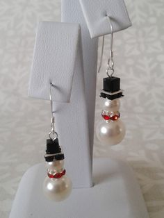 Sweet snowmen earrings made using Swarovski pearls and crystals with silver plated light red rhinestone spacers. All other components are sterling