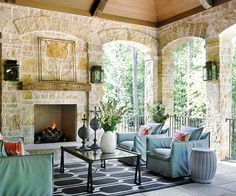 Style: Traditional A fireplace gives this outdoor room a more comfortable, homey feel. The traditional stone work offers timeless appeal and follows the design of the patio's archway openings. A wooden mantel adds another natural tone to the room, offers a nice change of pace in materials, and stands in contrast to the expanse of stone./