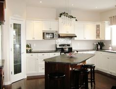 Decorations, Awesome Kitchen Remodeling Ideas With L Shaped White Laminate Kitchen Cabinet With Black Granite Top Microwave Shelf Kitchen Hood Under White Cabinet Crystal Pendant Lamp Wood Kitchen Island Table Wooden Round Bar Stools: Best Tips And Advice of Kitchen Remodeling for Your Home