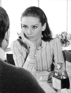 """The actress Audrey Hepburn (as Joanna Wallace) photographed by Terry O'Neill at the Restaurant Leï Mouscardins (on Rue Portalet) in St. Tropez (France), during the filming of """"Two for the Road"""", in May 1966. Audrey was wearing: Shirt: Ken Scott (inspired in a model by Cacharel and created specially for the wardrobe of her character Joanna Wallace)."""