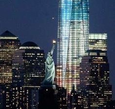 The Statue of Liberty with One World Trade Center lit up in red, white and blue lights ahead of the Fourth of July (© Julio Cortez/AP)