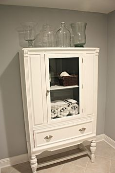 Painted/ transformed china cabinet for bathroom storage. Looks like it has been cut down to make it thinner.