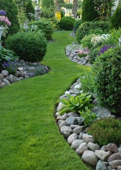 A stunning garden landscape, which can easily be replicated in your garden. Curved grass path with stone or rock edges, with beautiful flowers and sculped hedges to add height and interest. For another option you could have succulents growing in between the rocks