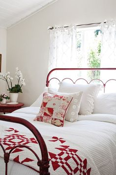 white bedroom with red metal bed frame and quilt at the foot of the bed- This is so pretty.