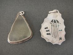 Sea glass set in sterling silver pierced with sea life. Front and back view.