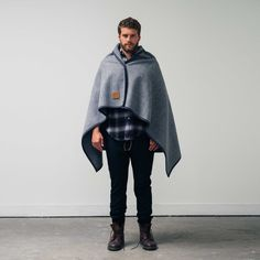 The WSw Utility Blanket revisits a classic Australian design, the original picnic blanket designed by Waverley Woollen Mills in the seventies.     Transitioning from a woollen blanket into a stylish throw over poncho with ease, the garment is fastened with black oxidised steel clasps, bordered in a dark hue of charcoal wool. Stamped with a branded leather patch!