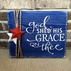 """Wooden Rustic Sign Memorial Day /Fourth of July """"God Shed His Grace On Thee"""". This is a beautiful blue stained 11"""" x 14"""" wooden sign. It has """"God Shed His a Grace On Thee"""" in permanent vinyl on it and is finished off with 2 stars and jute! Perfect for Memorial Day and Fourth of July!!."""