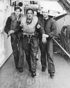 A survivor of German submarine U-175 is led below decks by crew members of USS Dwain, April 10, 1943.