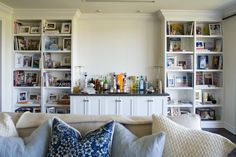 This soft hued living room features a small bar area with white cabinets and a gray granite countertop. Two white built-in bookshelves are positioned on either side, showcasing a number of books, framed photos and decorative pieces.