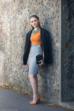 Kristina in ZARA emerald green statement necklace, orange top and heels, and heather gray pencil skirt.