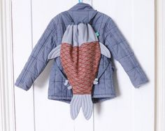 This drawstring backpack rucksack bag - in a shape of a Koi carp fish - is inspired from the Japanese Koinobori (kite in a shape of a fish). The body of the fish bag is made in a traditional (made in Japan) Japanese 100% cotton fabric printed with cream waves on a dark red background. The fins, the tail and the head parts are made in a plain soft grey slightly blue polyester cotton fabric (70% cotton and 30% polyester). The inside of the fish is entirely lined with a plain dark grey…