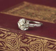 Circa 1930s Engagement Ring. Center old european cut diamond 2.85 carats. Unique bullet shaped side diamonds. Platinum