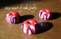 These bright red beads feature white and black waves slightly offset.  Beads by Heart of Oak Crafts (Etsy).