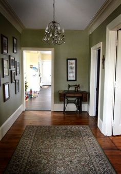Love the baseboard and the crown molding. The black frames against the green wall with white trim is so classic.  Paint color: Sherwin-Williams, Koi pond   May repaint the house this color