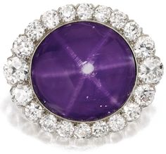 Platinum, Star Sapphire and Diamond Brooch, J.E. Caldwell, Circa 1910.    Centered by a plum-colored star sapphire weighing approximately 45.00 carats, framed by 22 round diamonds weighing approximately 5.35 carats, signed JEC & Co., numbered _2089. Sotheby's.