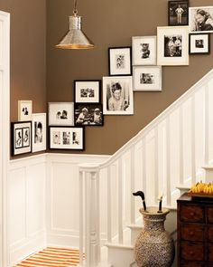 love this look...white moulding, wall color, photo arrangement up the stairs...maybe I should make it my mission this year to start collecting frames! :)