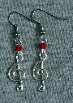 $10 Silver & Red Treble Clef Earrings. Made of non-tarnish, hypo-allergenic silver wire & a Swarovski crystal. The design of these earrings is simple but effective. Other colors available by request.
