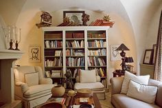 cozy book nook, with wild book arrangements! (love the gothic arched walls)
