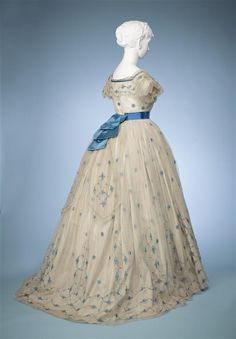 Ca.1865 evening dress (bodice, skirt, and belt) of white gauze embroidered with flowers in bright blue silk and trimmed with machine lace and bright blue satin ribbon