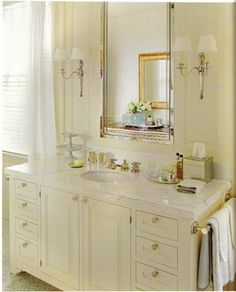 vanity next to window, mirror and sconces.