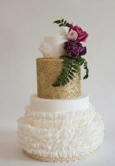 Breathtaking white and shimmering gold wedding cake topped with adorable flowers; Featured Cake: Heartsweet Cakes