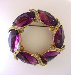 A purple glass wreath SPHINX brooch with rhinestones, and heavy vintage:  A lovely and substantial brooch signed SPHINX. The deep purple/burgundy color is rich in the precision-cut glass. There are clear rhinestones semi-woven between the glass forming an overall wreath design. A well constructed vintage piece.  Measurements: 2-3/8 in diameter and 1/2 wide. Signed: Sphinx Condition: Very good. A few of the rhinestones are darkening, no missing. Slight sporadic gold foil has empty spots. The…