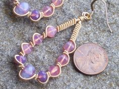 I have handcrafted these wire wrapped earrings from golden artistic wire. Very thin wire was wrapped around a thicker wire, and this in turn was wrapped between these gorgeous opalescent pink beads, and purple crystals. All together they seem to exude an opalescent glow. The earrings are