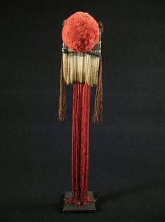 """This is a colorful bone hair comb from Vietnam that stands 18.5"""" high. It has a red cotton pompom and red and brown twisted silk dangling threads with black and white glass trade beads."""