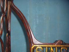 Kaki mesin jahit singer tua. Tampak detail besi tua yang masih kokoh sebagai penguat kaki siku-siku dan penyanggah merk singer