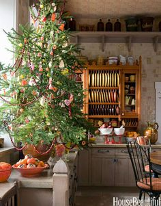 """""""The tree in the kitchen is edible, a tradition my mother kept when I was growing up. It's decorated with cookies, ribbon candy, gumdrops, and other old-fashioned candies that people can eat right off the tree,"""" says designer Barry Dixon. """"The strings of popcorn and cranberries go outside for the birds and squirrels when we're done. I love a big, glitzy tree, but the little ones really capture my heart every year.""""   - HouseBeautiful.com"""
