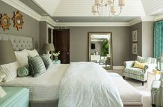 Punches of aqua augment the warm gray walls in the master bedroom. Tongue and groove paneling adorns the tray ceiling.  Paint: Winter Gates,...