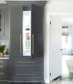 GRAY BLUE KITCHEN CABINETS: concealed #kitchen refrigerator in traditional cabinetry with #brass hardware