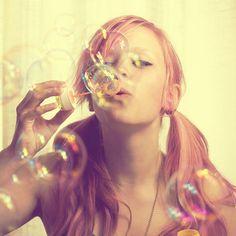 Фото Рыжеволосая девушка  с хвостиками дует мыльные пузыри