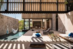 Elevated walls with marble slats form a canopy above the terrace and swimming pool of this house