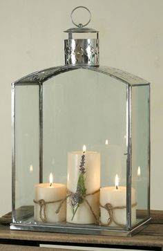 """This polished stainless steel lantern is 10"""" wide, 7"""" deep and 18"""" tall. It has glass sides, with one opening to replace candles.  A beautiful punched flower pattern decorates the top and around the chimney.  This can be so easily dressed up for Christmas with silk flower surround, bows, or just use your imagination. Holds three 3"""" dia candles that are not included. $99.95"""
