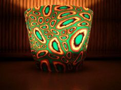 This is a beautiful one of a kind candle holder. Basically it's a glass covered with my polymer clay design.
