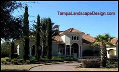 TampaLandscapeDesign.com Tuscan cypress enhance the Mediterranean architecture of this Lutz home.