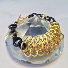 This bracelet has been made with black and gold coloured aluminium jump rings, making it light weight but still making a statement. This