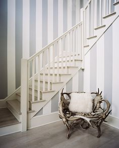 A striped entryway and staircase with a chair made of antlers