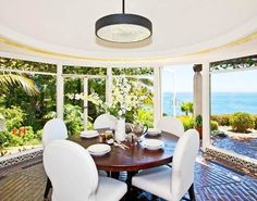 awesome breakfast nook with tile floor, round wood table surrounded by white upholstered chairs and glass walls showing off the beautiful ocean and garden views