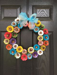 What a beautiful way to decorate your door for spring! This wreath is handmade out of Pinecones. Pinecones are cut into flower shape and hand painted in spring colors. Base is, 12in however finished wreath is about 17in. Bow is tied on and can be easily adjusted if you prefer bow placed at bottom of wreath.