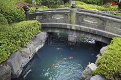 日本の石庭で赤魚と青い水の上の風光明媚な石の橋