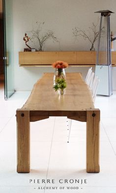 A Pierre Cronje custom bolted table with a single yellowwood plank top at the Delicatessan at Tokara Wine and Olive Farm.
