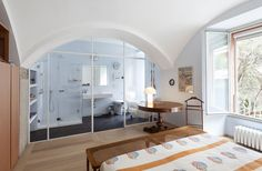 Projects:  An apartment in an old granary in Darsena, Milan  Master bedroom with en suite bathroom and sliding doors