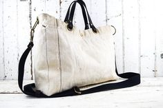 VINTAGE US NAVY MILITARY TOTE BAG - This bag was made from an older and rare US NAVY white (cream) canvas bag. This canvas is HEAVY, much heavier than the canvas bags that were made after these. The bag has original markings along with wear and tear, adding to the authenticity and character of the bag. The interior is heavy black canvas. The handles are thick black leather with about a 5 drop. The shoulder strap is fully adjustable and removable allowing you to wear the bag over the…
