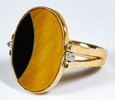 Lot 198: 18k Gold, Tiger Eye, Onyx and Diamond Ring; Having oval flat cut tiger eye and onyx flanked by round cut diamond chips; marked 18k and 750 inside band