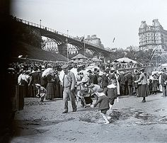 Scarborough, Yorkshire, England, UK. On the sands in the South Bay. The Grand Hotel is the large building on the right and that's the Spa Footbridge leading onto the South Cliff, to the left.  There's a large group of people giving their attention to beach entertainment, perhaps. The little girl and boys are busy playing with buckets and spades and another little girl is enjoying a donkey ride. The plate has a fault on the left-hand edge. I would date the photograph at circa 1910. Thi...