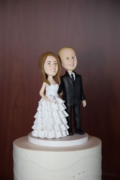 Custom wedding cake topper made to look just like the bride and groom!   Photo: AAVA Studio